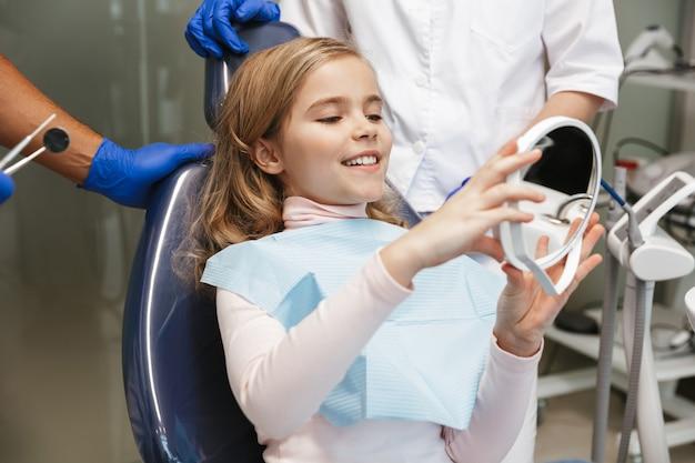 Милая счастливая красивая детская девочка, сидящая в медицинском стоматологическом центре, глядя в зеркало