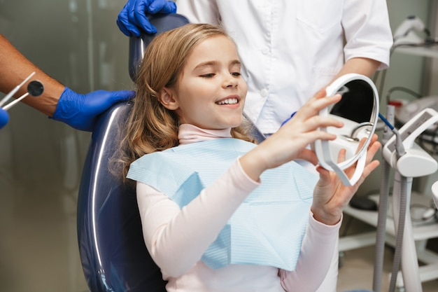 Cute happy beautiful child girl sitting in medical dentist center looking at mirror