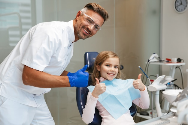 Cute happy beautiful child girl sitting in medical dentist center showing thumbs up