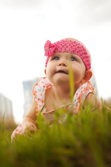 かわいい幸せな金髪の青い目の女の子6〜7ヶ月草の上を這って見上げる。教育、健康な子供時代、子育てのための概念的な写真。完璧な白人の幼児。セレクティブフォーカス