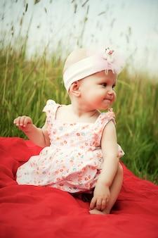 赤い格子縞の草の上に座って笑っている6〜7ヶ月のかわいい幸せな金髪の青い目の女の子。教育、健康な子供時代、子育てのための概念的な写真。完璧な白人の幼児。セレクティブフォーカス
