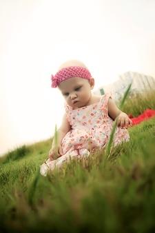 草の上に座って見下ろしている6〜7ヶ月のかわいい幸せな金髪の青い目の女の子。教育、健康な子供時代、子育てのための概念的な写真。完璧な白人の幼児。セレクティブフォーカス