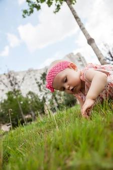 잔디에서 8 개월 된 귀여운 행복 한 금발 파란 눈 소녀. 교육, 건강한 어린 시절, 육아, 디자인 풍경에 대한 개념적 사진. 자연 여름에 완벽한 백인 유아입니다. 사이트 복사 공간