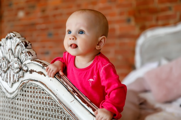 Cute happy blue-eyed 6-month-old girl in bright red dress at head of retro bed