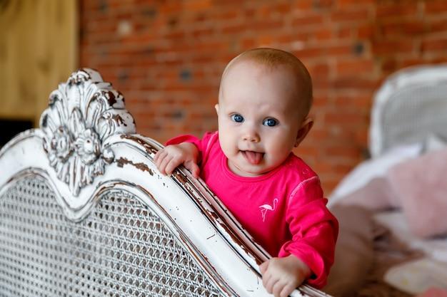 レトロなベッドの頭に真っ赤なドレスを着たかわいい幸せな青い目の生後6ヶ月の女の子。かなり笑顔の金髪美女。魅力的な子供はクローズアップで感情を示しています。健康な子供と子育ての概念