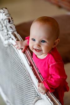 レトロなベッドの頭に真っ赤なドレスを着たかわいい幸せな青い目の生後6ヶ月の女の子