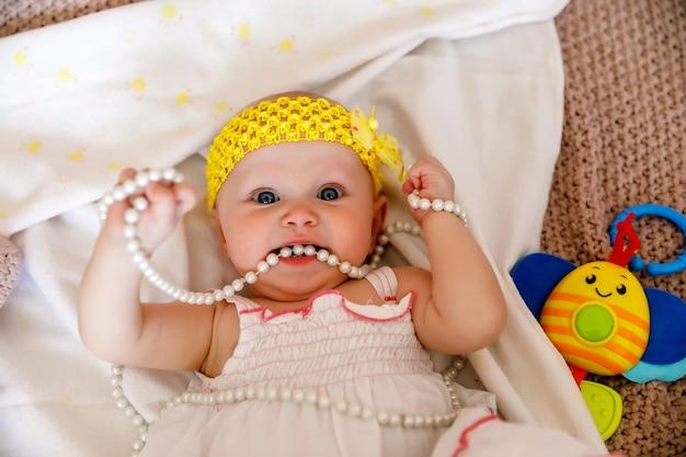 白いドレスを着たかわいい幸せな青い目の生後6か月の女の子は、ベッドの上で真珠ビーズで遊んでいます。かなり笑顔の金髪美女。魅力的な子供はクローズアップで感情を示しています。健康な子供と子育ての概念