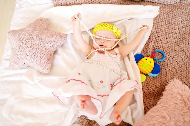 白いドレスを着たかわいい幸せな青い目の6ヶ月の女の子は、ベッドの上で真珠ビーズで遊ぶ