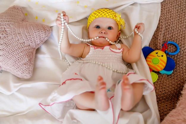 白いドレスを着たかわいい幸せな青い目の生後6ヶ月の女の子は、ベッドの上で真珠ビーズで遊ぶ