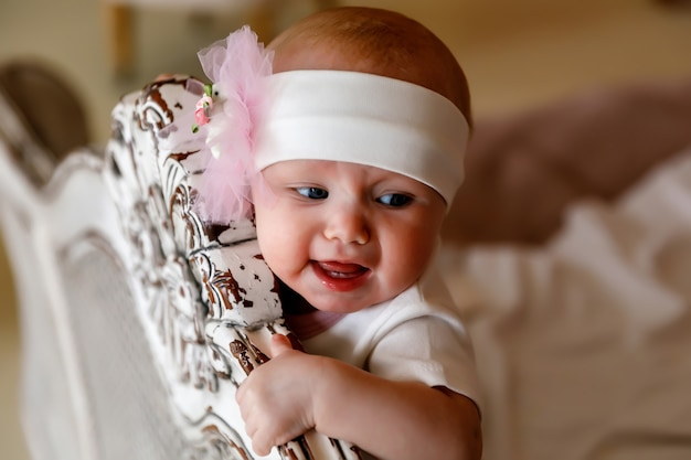 レトロなベッドの頭に白いヘッドバンドでかわいい幸せな青い目の生後6ヶ月の女の子