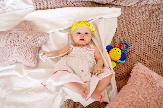 Cute happy blue-eyed 6-month-old girl in white dress plays with pearl beads on bed