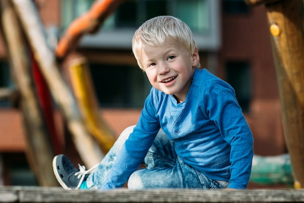 Cute happy boy with blond hair having fun on the playground on sunny summer day .