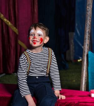 Милый счастливый мальчик с клоунским макияжем сидит на сцене перед представлением в полосатой рубашке с длинным рукавом и подтяжками