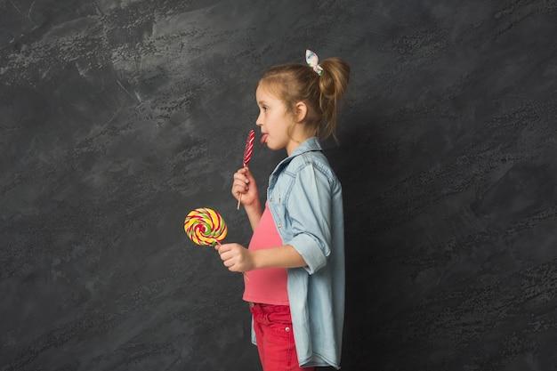 キャンディケインのロリポップを持って、黒いスタジオの背景、側面図、コピースペースで楽しんでいるかわいい幸せなカジュアルな女の子。女性の子供の表情