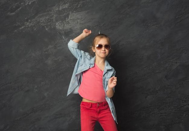 黒のスタジオの背景、コピースペースで楽しんでサングラスでかわいい幸せなカジュアルな女の子。女性の子供の表情