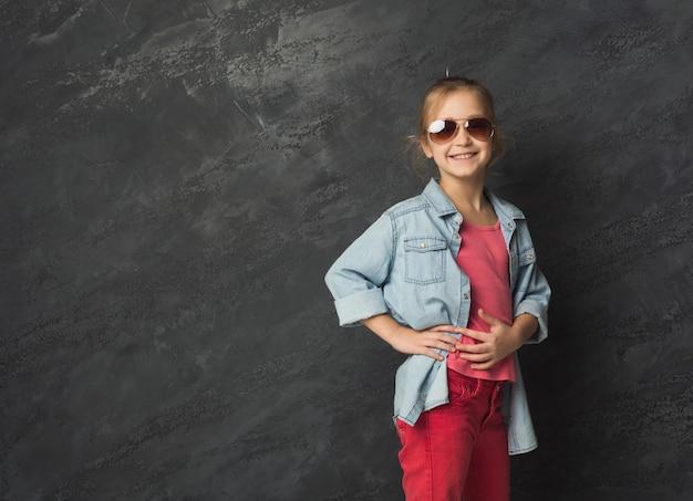 黒のスタジオの背景、コピースペースでポーズをとるサングラスのかわいい幸せなカジュアルな女の子。女性の子供の表情、コピースペース