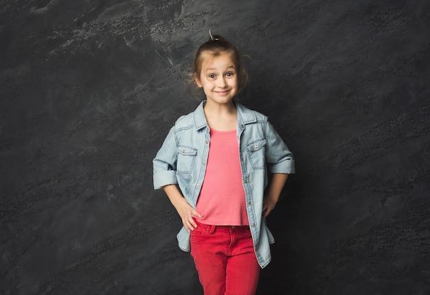 黒のスタジオの背景、コピースペースでポーズをとってかわいい幸せなカジュアルな女の子。女性の子供の表情、コピースペース
