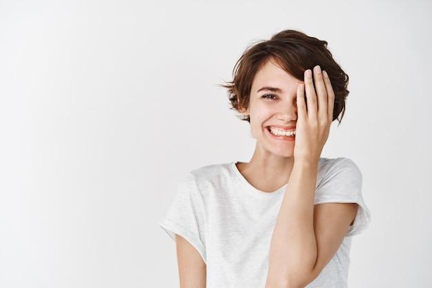 Donna caucasica carina e felice in t-shirt, copre metà del viso e sorride, in piedi contro il muro bianco