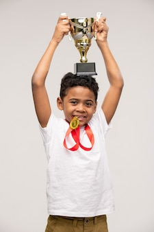 Cute happy champion of african ethnicity holding golden medal by teeth and keeping cup of winner on his head