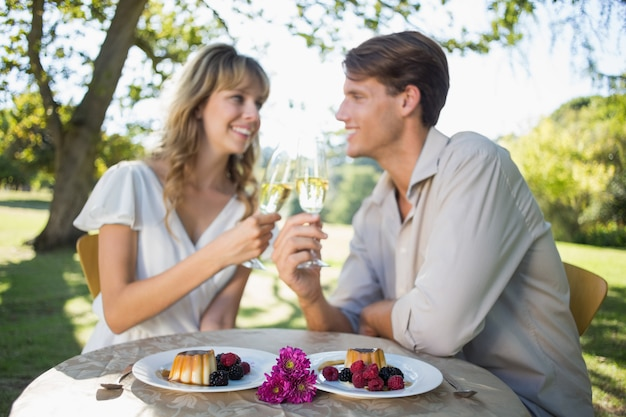 Cute happy couple sitting outside toasting with champagne with dessert