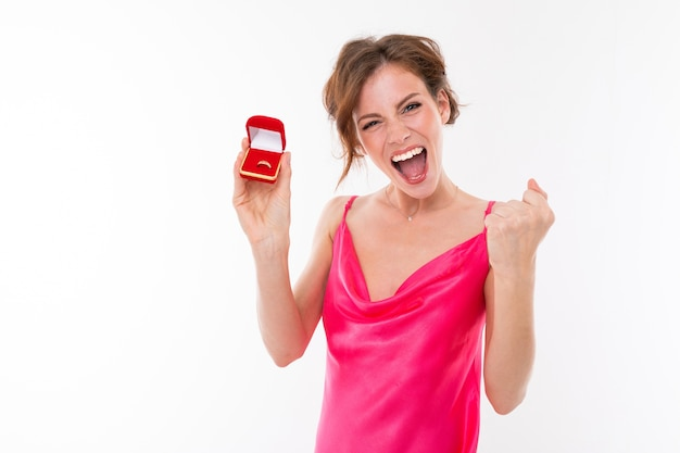 Cute happy emotional girl with makeup in a pink dress shows a box with a ring on a white background.