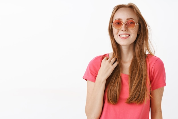 Cute happy and emotive young redhead female in pink sunglasses and t-shirt touching strand of hair and smiling feeling awkward in unfamiliar company trying start conversation friendly