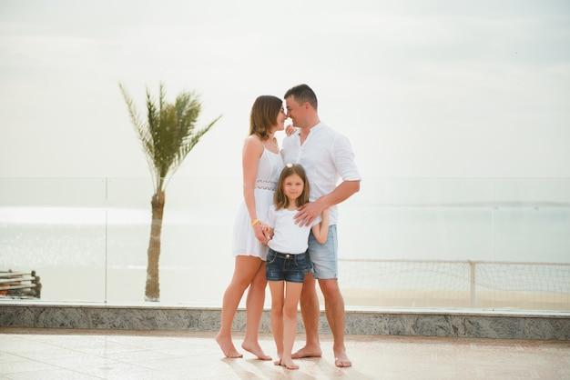Милая счастливая семья весело на роскошном тропическом курорте, летние каникулы, концепция любви