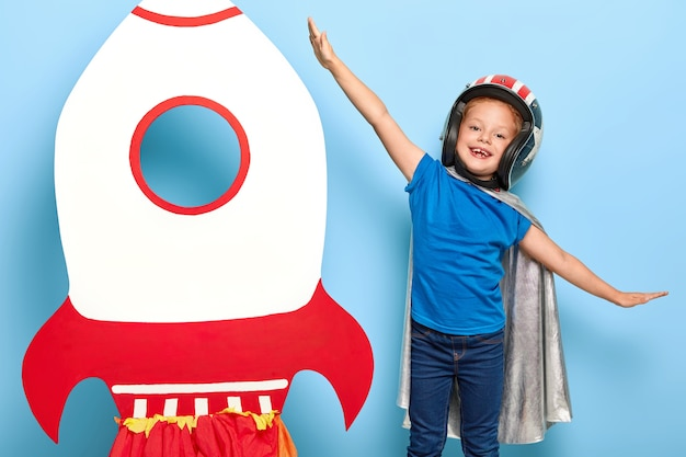 Cute happy female child plays astronaut, wears flying helmet and cape