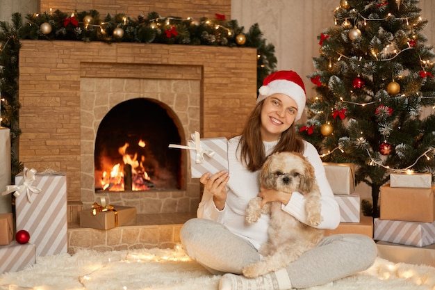 Cute happy female sitting on floor with crossed legs, showing to camera her christmas present box and hugging her dog, wearing casual attire and red hat.