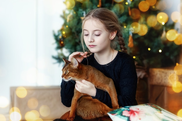 A cute happy girl hugs an abyssinian cat on the background of a new year tree there are lights