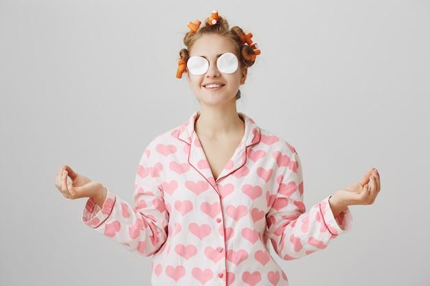 ナイトウェアとヘアカーラーでかわいい幸せな女の子は、綿のパッドで化粧を拭き取ります