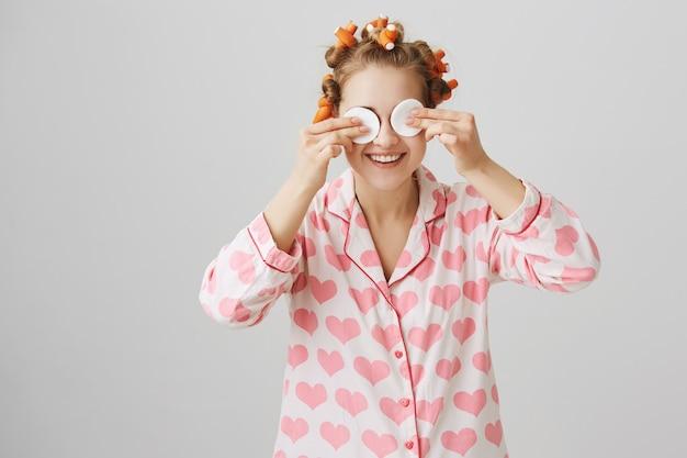 Carina ragazza felice in indumenti da letto e bigodini trucco con tamponi di cotone
