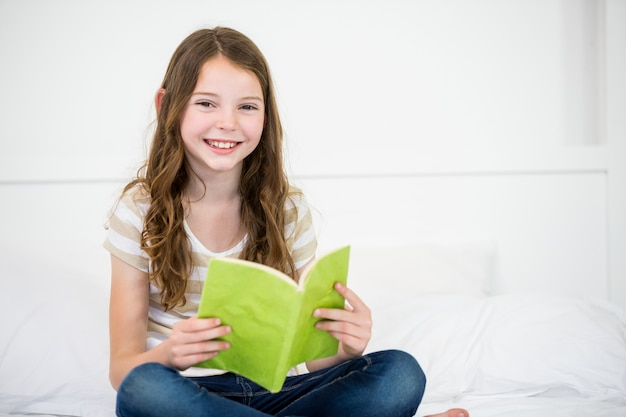 Cute happy girl reading book on bed
