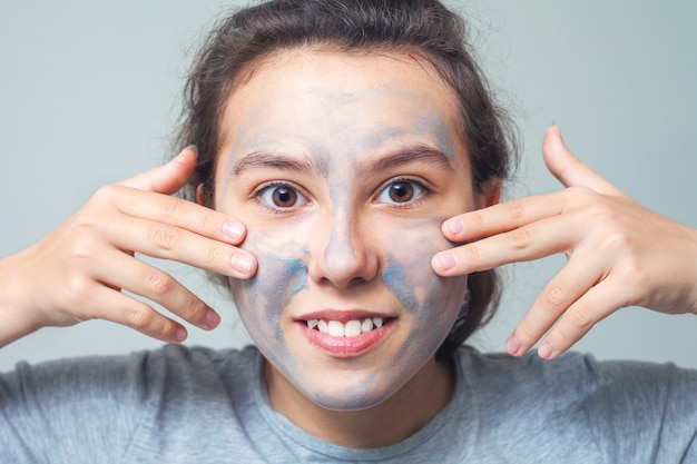 Cute and happy girl smears face with cosmetic clay or mud and smiles. cosmetic mask, face scrub.