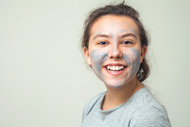 Cute and happy girl smears face with cosmetic clay and smiles