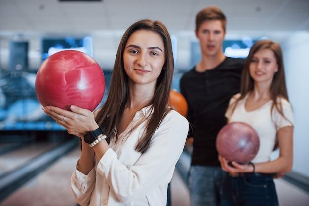 Carina ragazza felice. i giovani amici allegri si divertono al bowling durante i fine settimana
