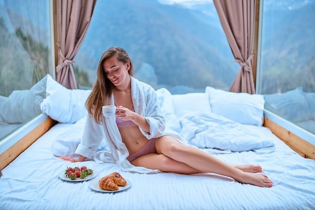 Милая счастливая великолепная улыбающаяся женщина с красивым телом и стройными длинными ногами в нижнем белье и халате сидит на мягкой белой кровати с большими окнами во время утреннего завтрака. начало нового дня
