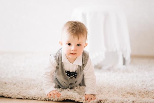 Милый счастливый малыш в стильном джентльменском костюме ползет по дому