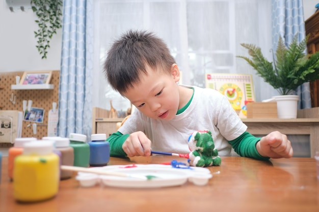 Cute happy little asian 3 - 4 years old toddler boy child  painting color on diy plaster painting toy, 3d plaster statue indoor at home, creative play for kids and toddlers concept - selective focus