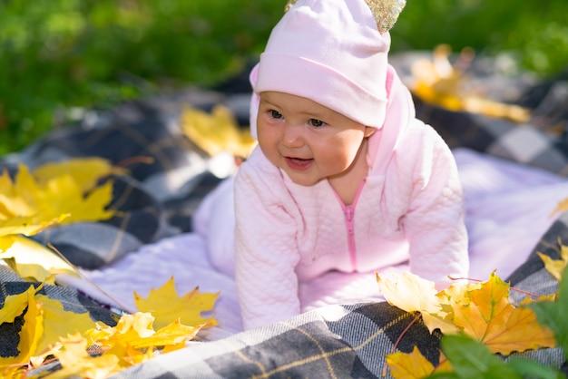 Милая счастливая маленькая девочка в розовом наряде играет на открытом воздухе осенью на коврике на траве в окружении разноцветных желтых листьев