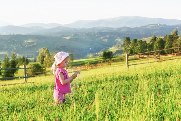 かわいい幸せな小さな女の赤ちゃんは、早朝に芝生と山の景色を眺めながら屋外で遊ぶ。テキスト用のスペースをコピー
