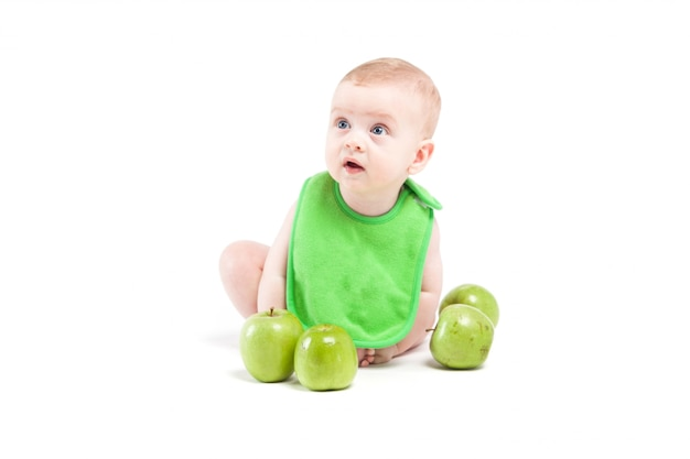 Cute happy little boy in green bib near green apples