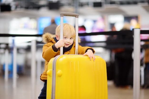 Cute happy little boy with big yellow suitcase at international airport before flight
