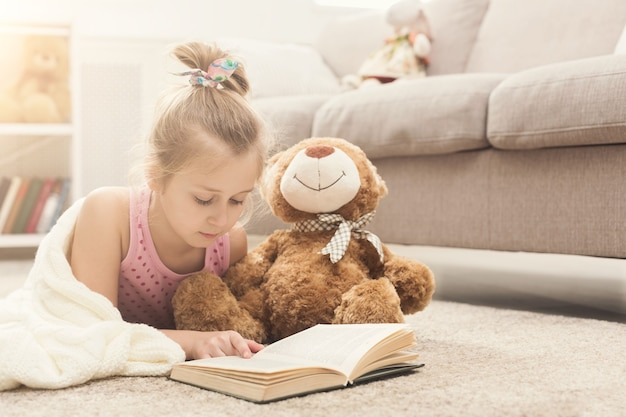 テディベアを抱きしめて本を読んで、白い毛布に包まれたかわいい幸せな小さなカジュアルな女の子。彼女のお気に入りのおもちゃ、コピースペースと一緒にソファの近くの床に横たわって、家にいるかわいい子供