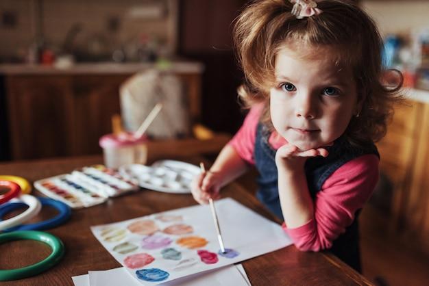 Милая счастливая маленькая девочка, прелестный дошкольник, рисующий с водой