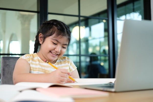 Cute and happy little girl children using laptop computer, studying through online e-learning system.