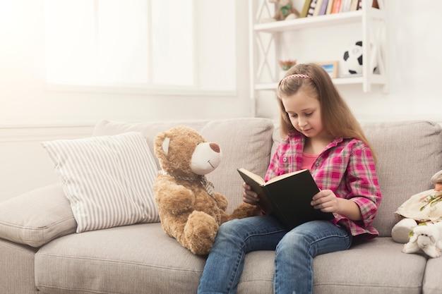 テディベアを抱きしめて本を読んでかわいい幸せな少女。彼女のお気に入りのおもちゃ、コピースペースと一緒にソファに座って、家でかわいい子供
