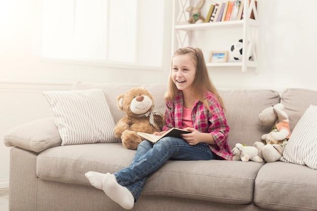 テディベアを抱きしめて本を読んでかわいい幸せな少女。家にいるかわいい子供、お気に入りのおもちゃを持ってソファに座って、楽しい時間を過ごして、スペースをコピーする