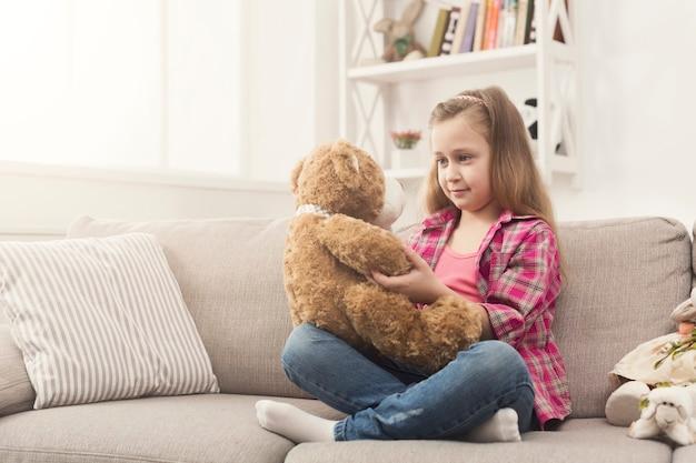テディベアを抱きしめるかわいい幸せな少女。彼女のお気に入りのおもちゃ、コピースペースと一緒にソファに座って、自宅できれいな女性の子供