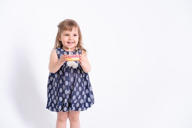 흰색 바탕에 촛불 생일 케이크 도넛 블루 드레스에 귀여운 행복 한 어린 소녀.